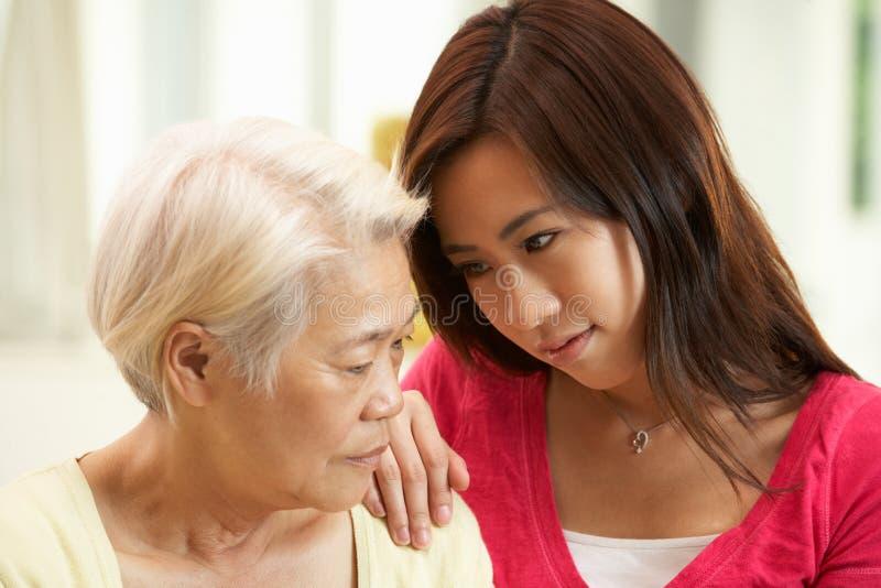 Madre china infeliz que es confortada por Daughter fotos de archivo