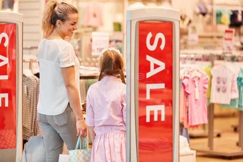 Madre con compras de la hija mientras que en venta fotografía de archivo