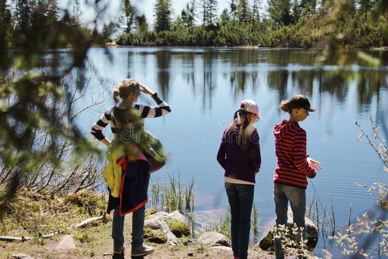 Madre con dos hijas en un viaje cerca del lago de la montaña - tener ocio imagen de archivo