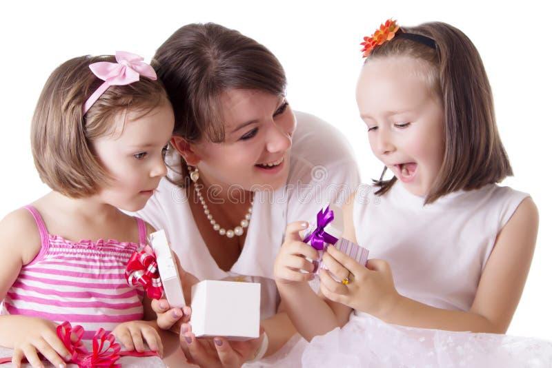 Madre con dos hijas que ofrecen la caja de la sorpresa foto de archivo