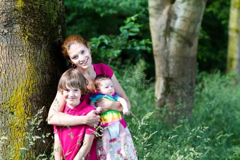 Madre con dos niños en un paseo en el bosque fotografía de archivo libre de regalías