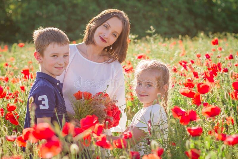 Madre con dos niños entre campo rojo de la amapola foto de archivo libre de regalías
