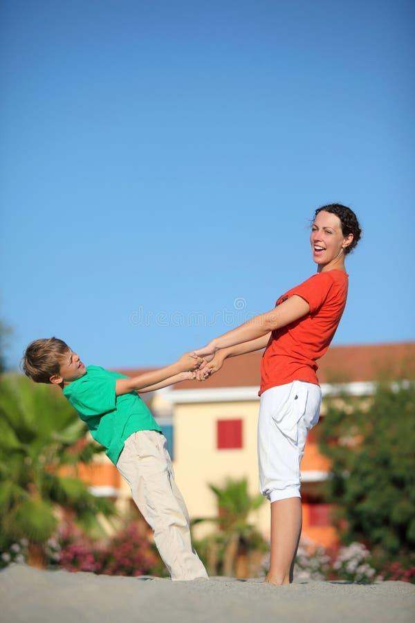 Madre con el aferrar del hijo a las manos y al juego en la arena fotografía de archivo libre de regalías