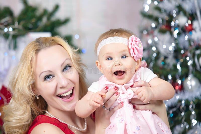Madre con el bebé delante del árbol de Navidad Retrato de la familia de la Navidad imágenes de archivo libres de regalías