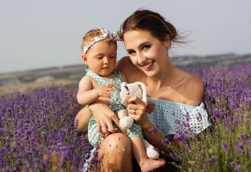 Madre con el bebé en campo púrpura de la lavanda fotos de archivo