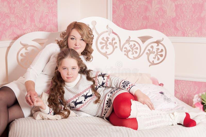 Madre con el bebé en el sofá, fondo rosado fotos de archivo libres de regalías