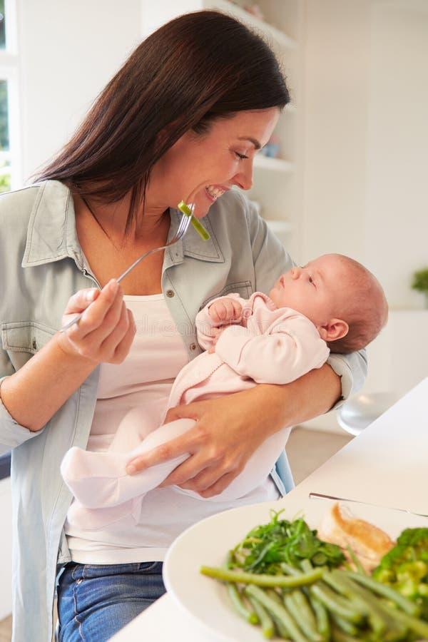 Madre con el bebé que come la comida sana en cocina fotos de archivo