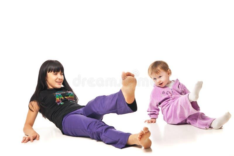 Madre con el bebé que hace ejercicios sobre blanco foto de archivo libre de regalías