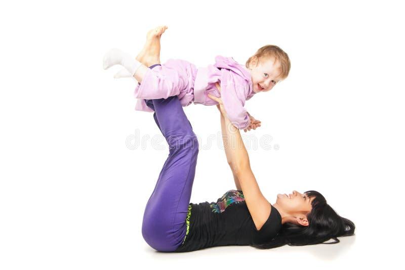 Madre con el bebé que hace ejercicios sobre blanco imágenes de archivo libres de regalías