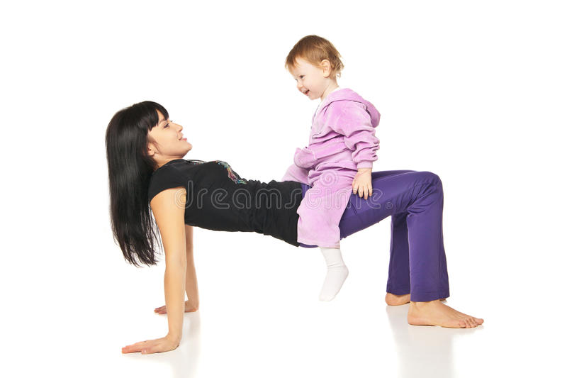 Madre con el bebé que hace ejercicios sobre blanco fotografía de archivo