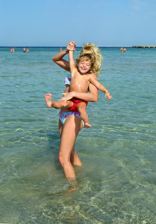 Madre con el bebé que juega en la playa foto de archivo libre de regalías