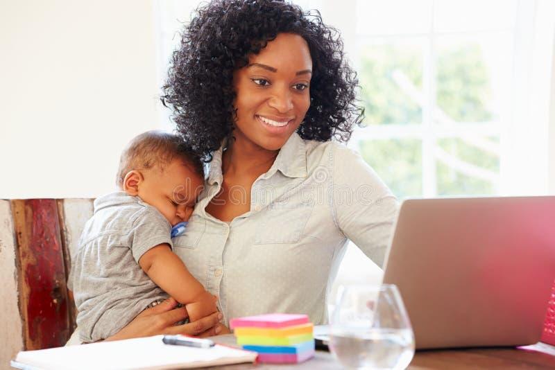 Madre con el bebé que trabaja en oficina en casa fotos de archivo libres de regalías