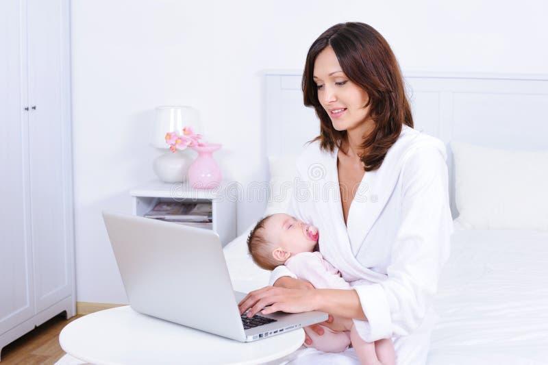 Madre con el bebé que usa la computadora portátil en sitio fotos de archivo