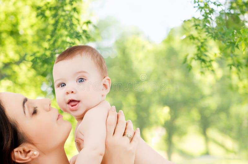 Madre con el bebé sobre fondo natural verde fotos de archivo libres de regalías