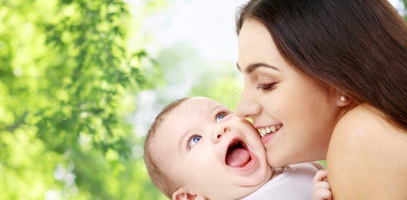 Madre con el bebé sobre fondo natural verde imagen de archivo