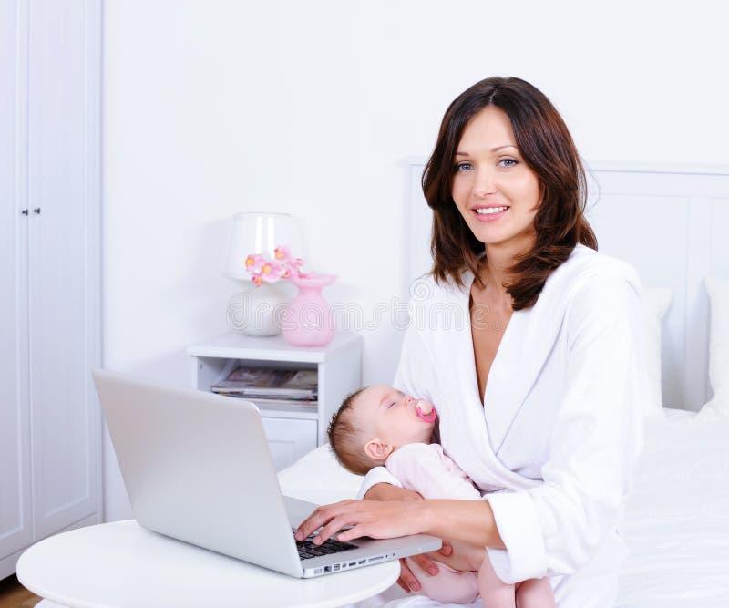 Madre con el bebé y con la computadora portátil en el país foto de archivo libre de regalías