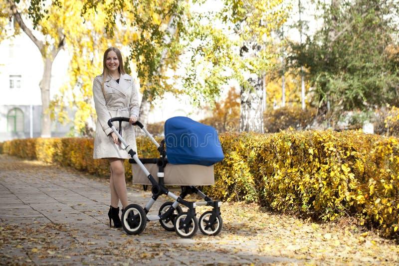 Madre con el cochecito de bebé para un recién nacido foto de archivo