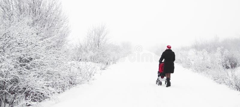 Madre con el cochecito de niño en invierno fotografía de archivo
