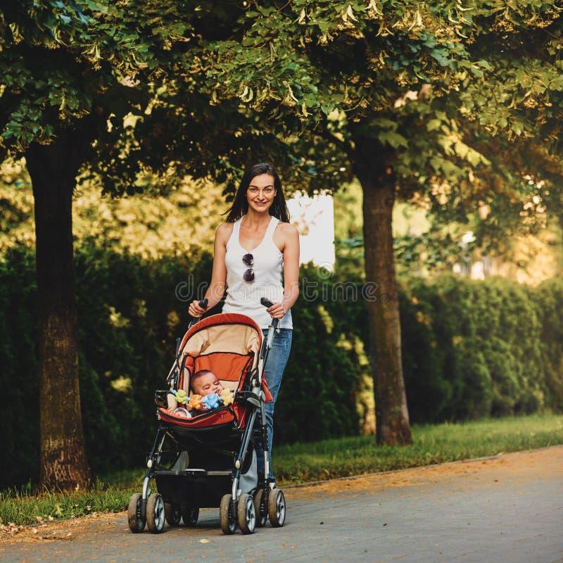 Madre con el cochecito de niño en parque fotos de archivo