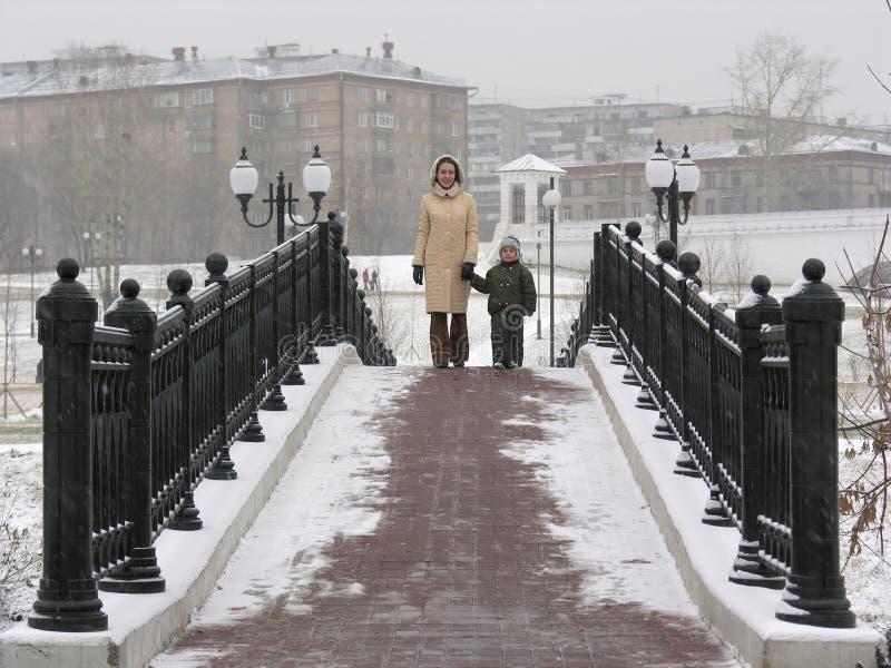Madre con el hijo en el puente del invierno fotos de archivo