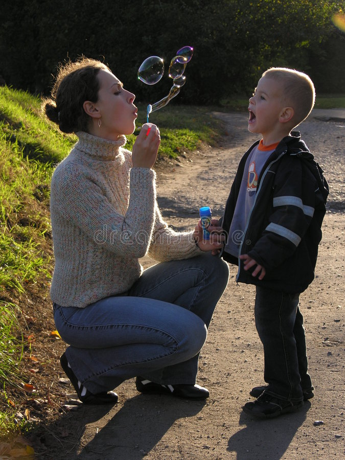 Madre con el hijo en ocaso con la burbuja jabonosa fotografía de archivo libre de regalías