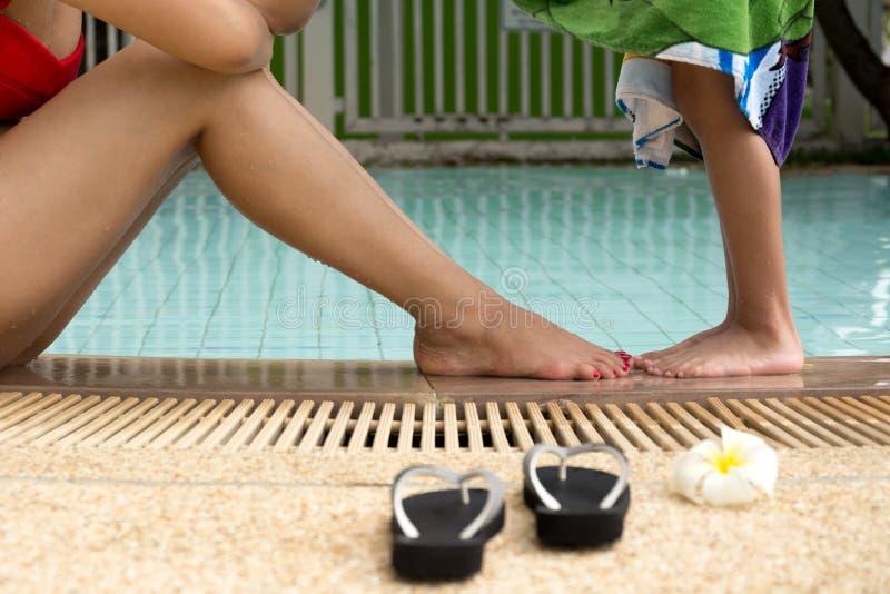 Madre con el hijo que juega al borde de la piscina con sandalia y fotografía de archivo
