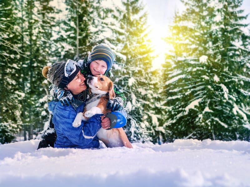 Madre con el hijo y el perro que juegan junto en bosque de la nieve foto de archivo