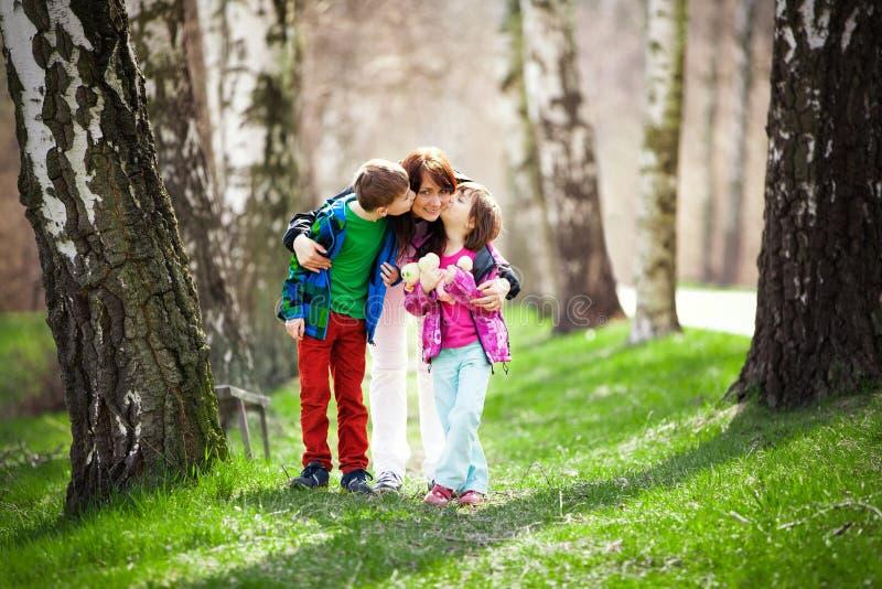 Madre con el hijo y la hija en bosque foto de archivo