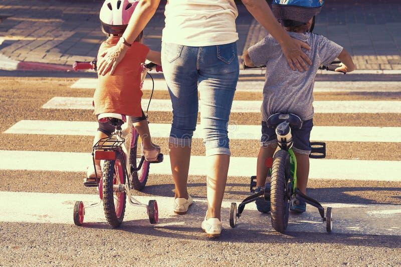 Madre con el hijo y la hija con una bici en una cebra fotos de archivo
