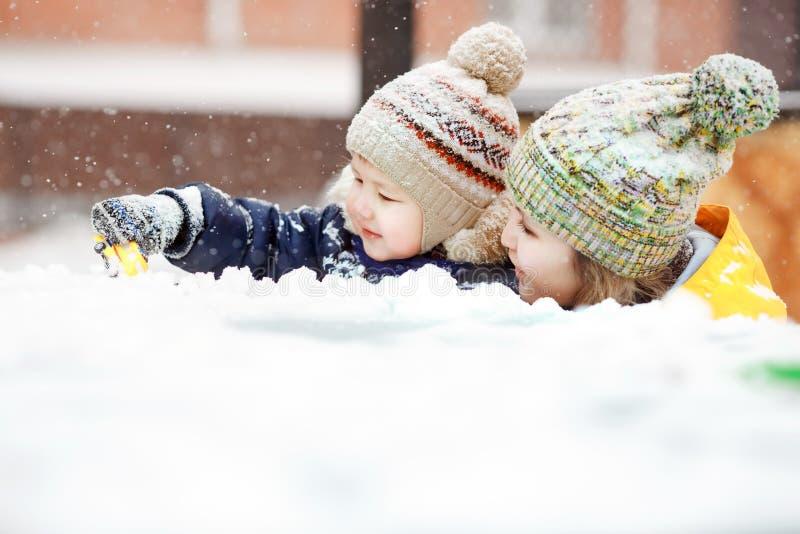 Madre con el juego de niños en nieve en el paseo del invierno, emociones positivas, al aire libre Nevadas, ventisca fotos de archivo