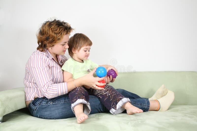 Madre con el niño en el sofá fotos de archivo libres de regalías