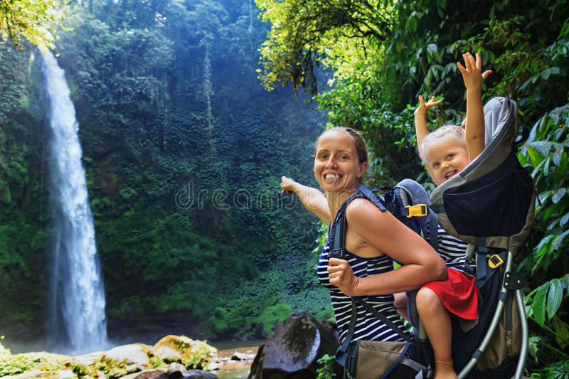 Madre con el niño en la mochila que camina a la cascada de la selva imagen de archivo libre de regalías