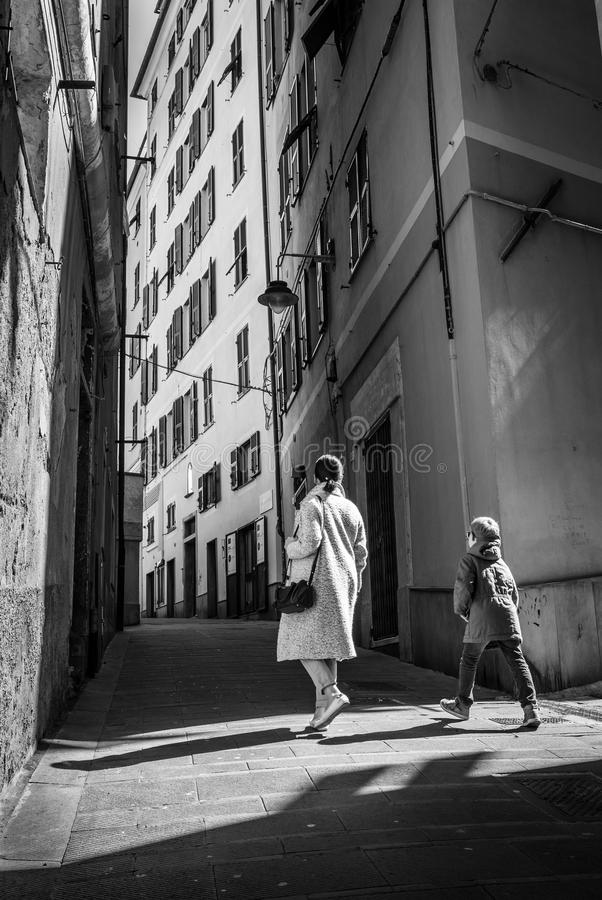 Madre con el pequeño hijo que camina por las calles italianas viejas estrechas foto de archivo