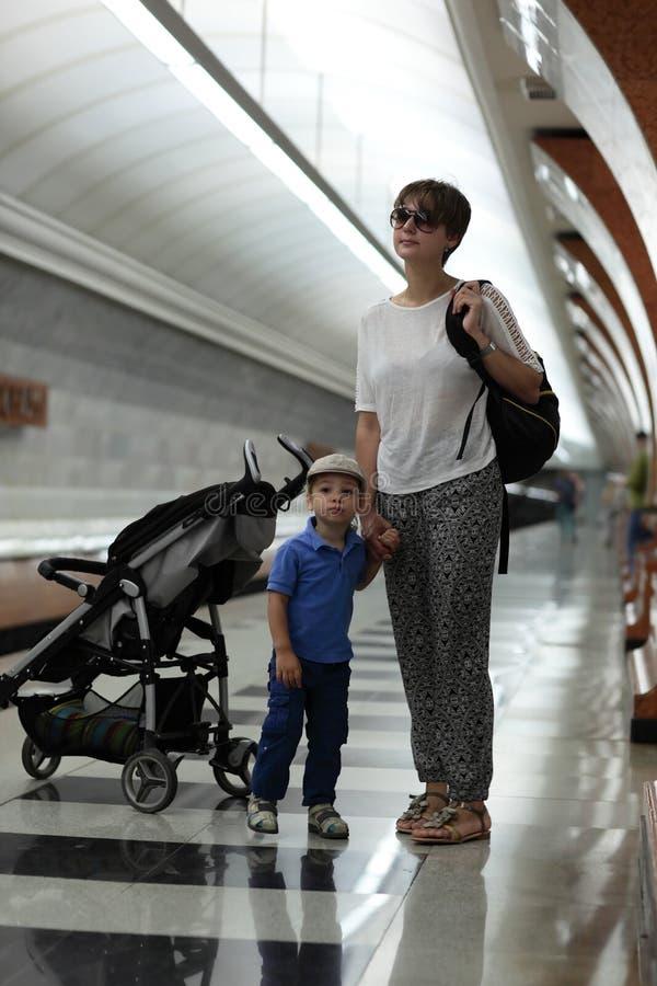 Madre con el tren que espera del hijo foto de archivo