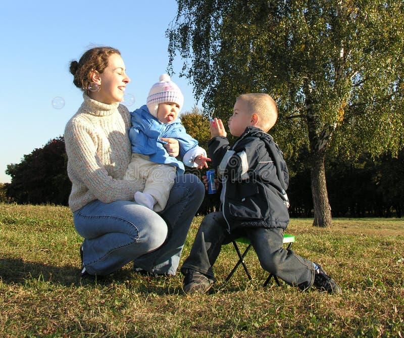 Madre con i bambini e le bolle fotografia stock