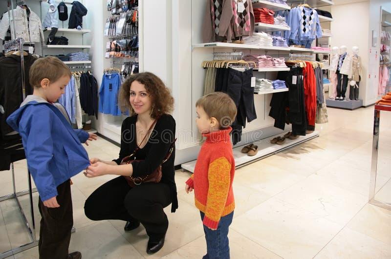 Madre con i bambini nel negozio dei vestiti fotografia stock libera da diritti