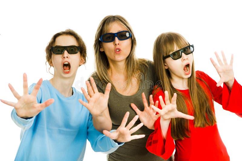 Madre con i bambini con i vetri del cinema 3D - prestazione di sorveglianza spaventata - gesti di stupefazione fotografia stock