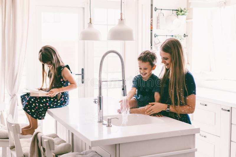 Madre con i suoi bambini che giocano nel lavandino di cucina fotografie stock libere da diritti