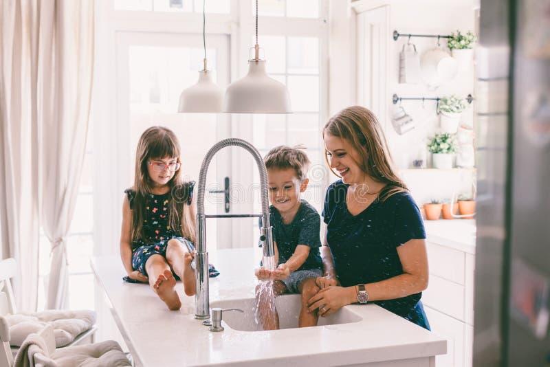 Madre con i suoi bambini che giocano nel lavandino di cucina fotografia stock libera da diritti
