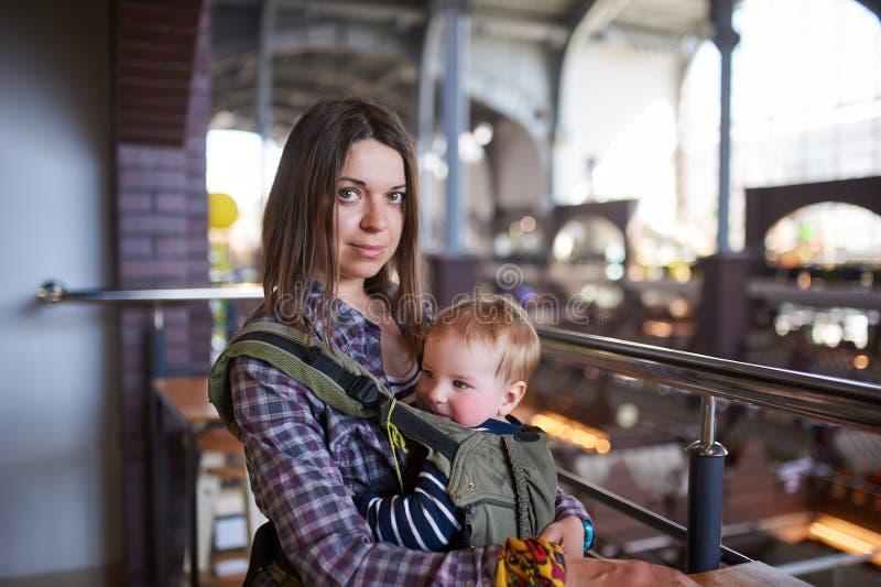 Madre con il bambino di trasporto ergobaby in caffè fotografia stock libera da diritti