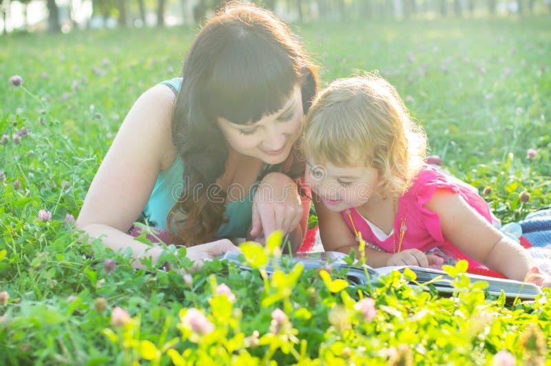 Madre con il bambino nel resto della natura sull'erba immagini stock libere da diritti