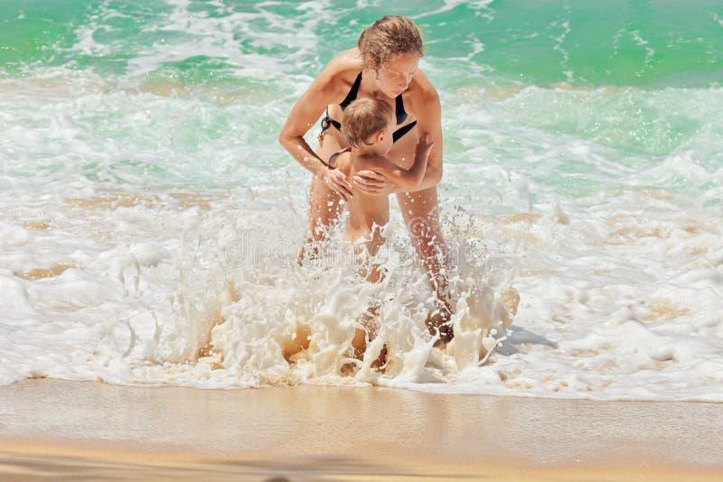 Madre con il bambino nelle onde del mare fotografia stock libera da diritti