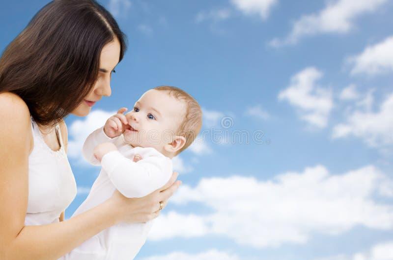 Madre con il bambino sopra il fondo del cielo fotografia stock