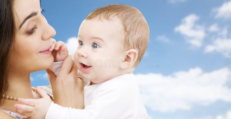 Madre con il bambino sopra il fondo del cielo fotografia stock libera da diritti