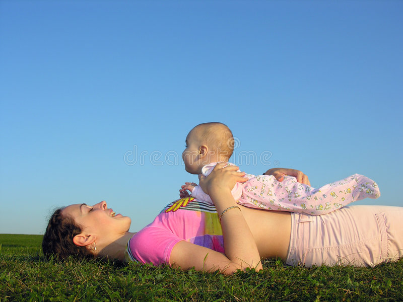 Madre con il bambino sulla bugia di tramonto immagini stock