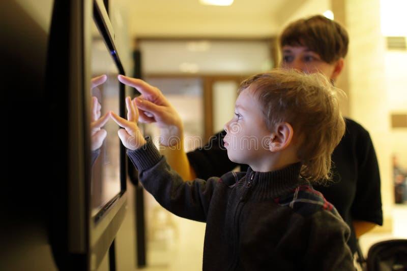 Madre con il figlio che per mezzo del touch screen fotografia stock libera da diritti