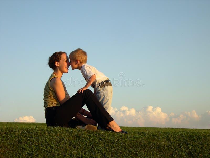 Madre con il figlio sul bacio del tramonto dal radiatore anteriore fotografia stock libera da diritti