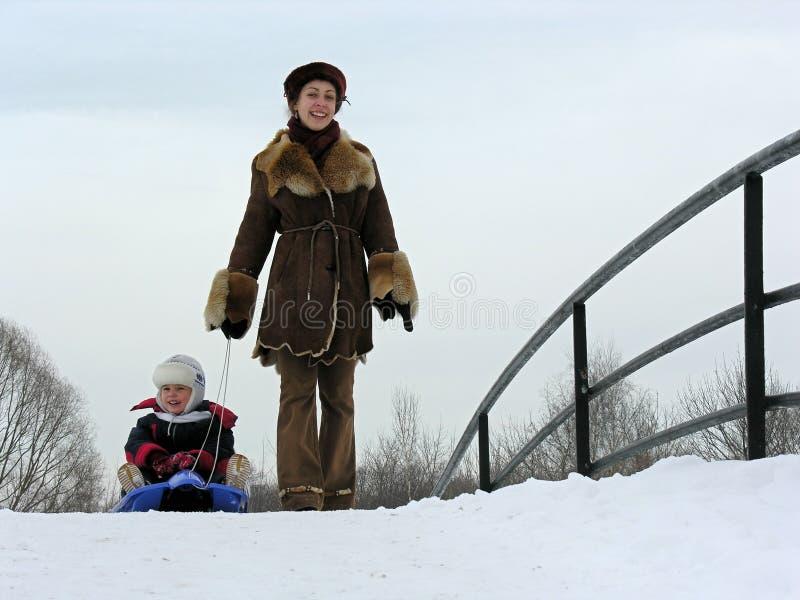 Madre con il figlio sulla slitta. fotografia stock libera da diritti