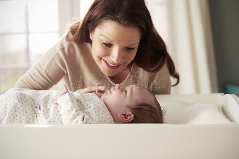 Madre con il neonato che si trova sulla Tabella cambiante in scuola materna fotografie stock libere da diritti
