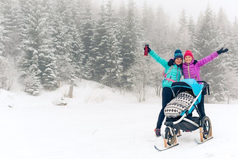 Madre con il passeggiatore di bambino che gode della foresta di inverno con l'amico o il partner femminile, tempo della famiglia  immagine stock libera da diritti